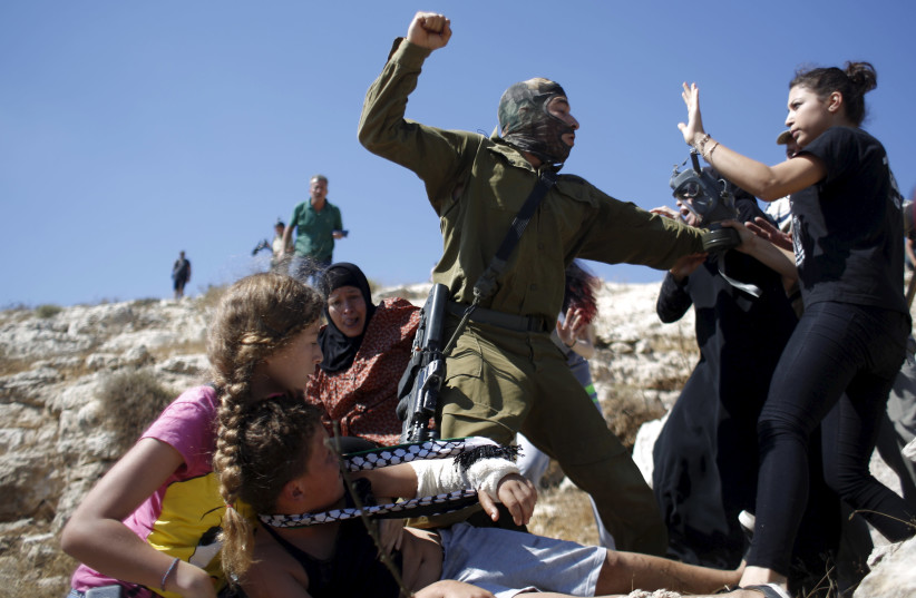 The Tamimi family scuffles with an Israeli soldier as they try to prevent him from detaining a boy during a protest against Jewish settlements in the West Bank village of Nabi Saleh, August 28, 2015 (photo credit: MOHAMAD TOROKMAN/REUTERS)