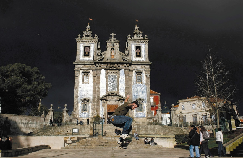 A boy performs with his skateboard in front of Santo Ildefonso Church at Batalha Square in Porto, northern Portugal (photo credit: REUTERS)