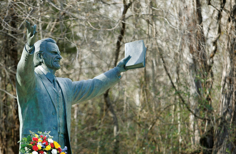 A Garland sits under a large bronze statue of evangelist Billy Graham on the grounds of a Christian conference center in Ridgecrest, North Carolina (photo credit: REUTERS)