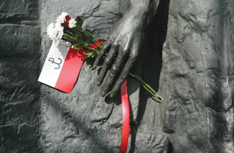 A FLAG and flowers are left at a monument in Warsaw, Poland that commemorates the uprising in the city's Jewish ghetto in 1944. (photo credit: REUTERS)