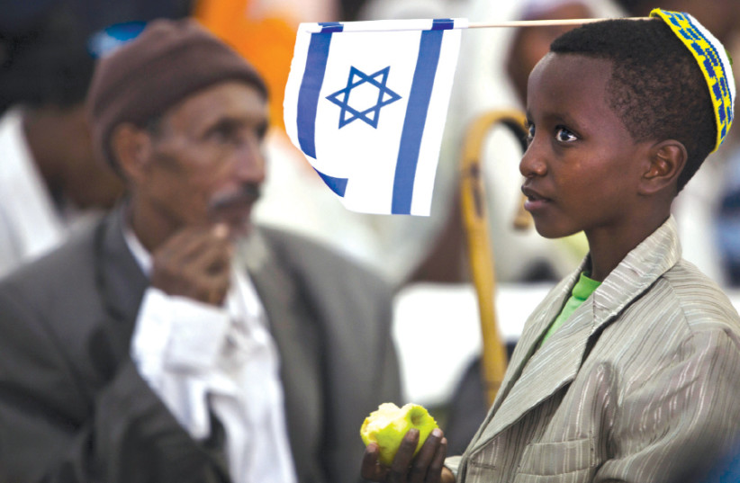 A YOUNG immigrant from Ethiopia waits upon his arrival at Ben-Gurion in 2012 (photo credit: REUTERS/NIR ELIAS)