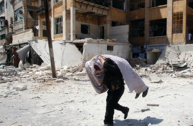 A FREE Syrian Army  ghter carries the body of a fellow  ghter during clashes in Aleppo in August 2012 (photo credit: GORAN TOMASEVIC/REUTERS)