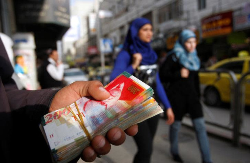 Palestinian women walk past a money changer in the West Bank city of Ramallah February 16, 2010. REUTERS/Mohamad Torokman/File Photo (photo credit: REUTERS/MOHAMAD TOROKMAN)
