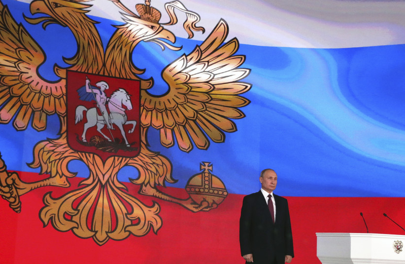 Russian President Vladimir Putin stands on the stage as he addresses the Federal Assembly in Moscow, Russia March 1, 2018 (photo credit: SPUTNIK/MIKHAIL KLIMENTYEV/KREMLIN VIA REUTERS)