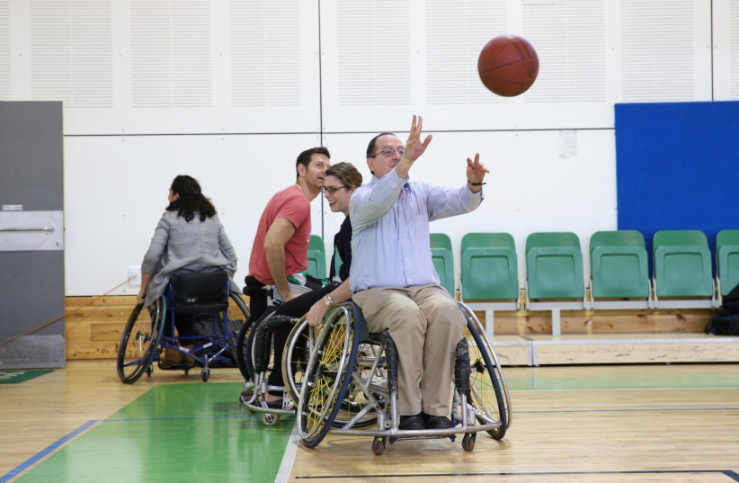 David Schizer, JDC CEO, plays basketball with disabled Israelis at the Spivack gymnasium in Ramat Gan. The game, last month, was a part of a program aimed at integrating people with disabilities into Israeli society through sport (photo credit: CHEN GALILI FOR JDC)