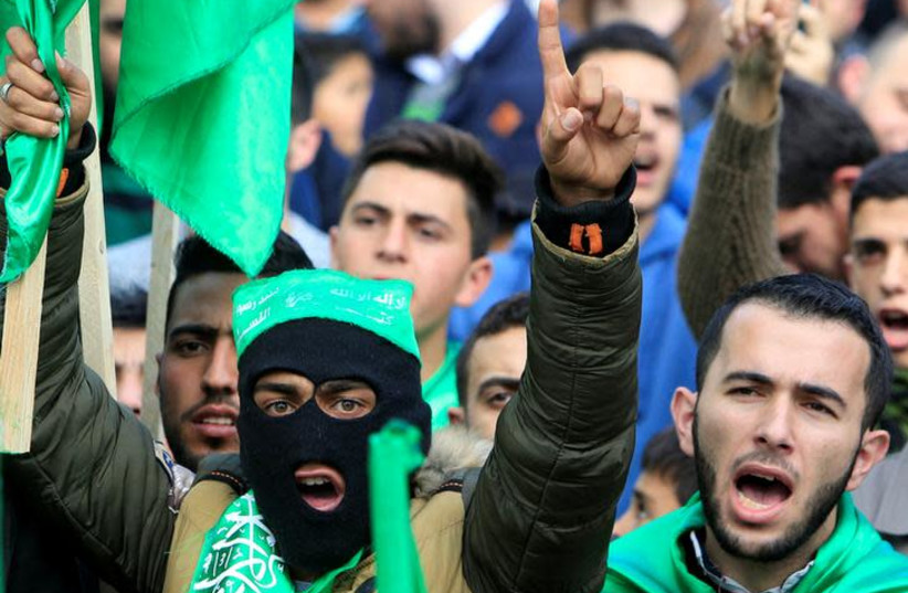 Palestinian Hamas supporters shout slogans during a rally marking the 30th anniversary of Hamas' founding, in the West Bank city of Nablus December 15, 2017. REUTERS/Abed Omar Qusini (photo credit: ABED OMAR QUSINI/REUTERS)
