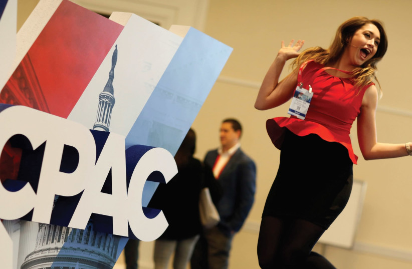 A WOMAN jumps in front of the Conservative Political Action Conference (CPAC) sign at National Harbor, Maryland, last month. (photo credit: REUTERS)