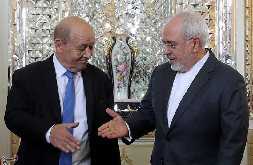 Iranian Foreign Minister Mohammad Javad Zarif reaches out to shake hands with French Foreign Affairs Minister Jean-Yves Le Drian in Tehran, Iran, March 5, 2018. (photo credit: REUTERS)