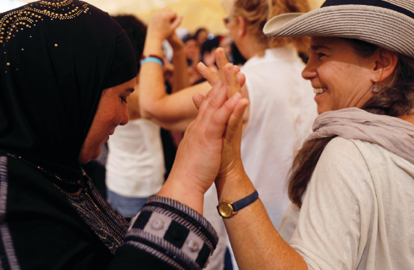 Women celebrate inside a peace tent erected as part of an event organized by 'Women Wage Peace,' near the Jordan River on October 8, 2017 (photo credit: RONEN ZVULUN/REUTERS)