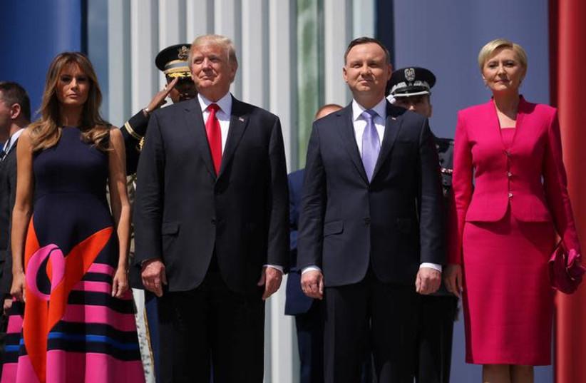 U.S. President Donald Trump stands next to First Lady Melania Trump, Polish President Andrzej Duda and Polish First Lady Agata Kornhauser-Duda before his public speech at Krasinski Square, in Warsaw, Poland July 6, 2017. (photo credit: REUTERS/CARLOS BARRIA)