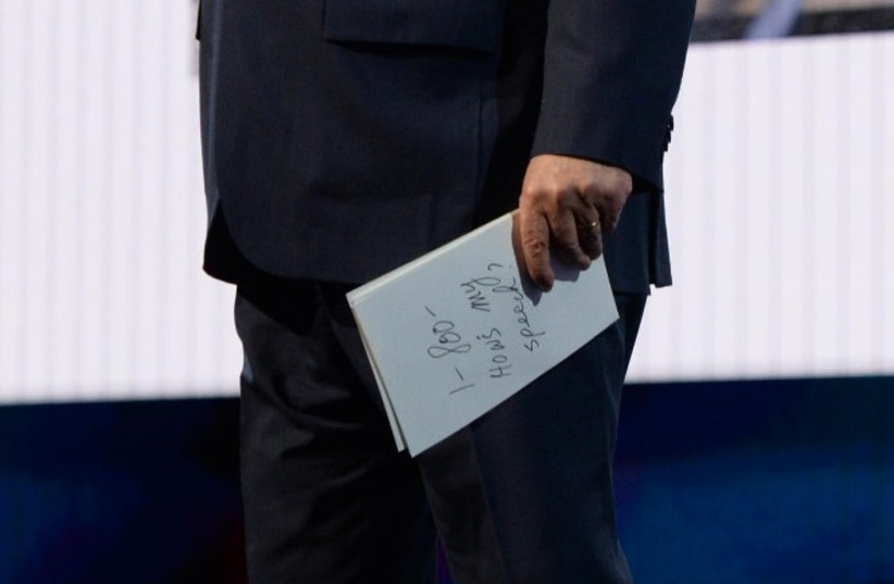 """Prime Minister Benjamin Netanyahu holds a booklet showing """"1-800 How's My Speech?"""" at AIPAC Conference (photo credit: CHAIM TZACH/GPO)"""