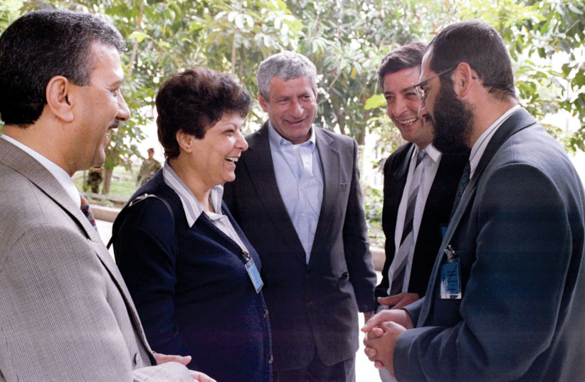 Leila Khaled smiles while talking to delegates outside a Palestinian National Council meeting in the Gaza Strip in the 1990s (photo credit: REUTERS)