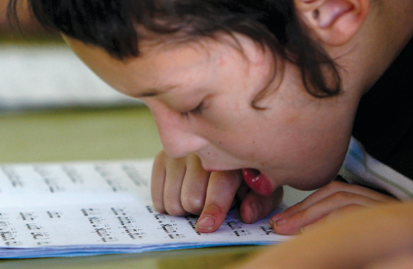 A HAREDI child reads from the Bible during a reading class at the Kehilot Ya'acov Torah School for boys in Jerusalem in 2010 (photo credit: RONEN ZVULUN / REUTERS)