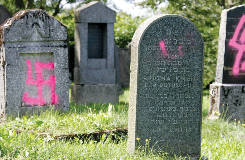 GRAVES DESECRATED by vandals with Nazi swastikas and antisemitic slogans are seen in the Jewish cemetery of Weyhers, near the western German town of Ebersburg in 2005 (photo credit: FABRIZIO BENSCH / REUTERS)