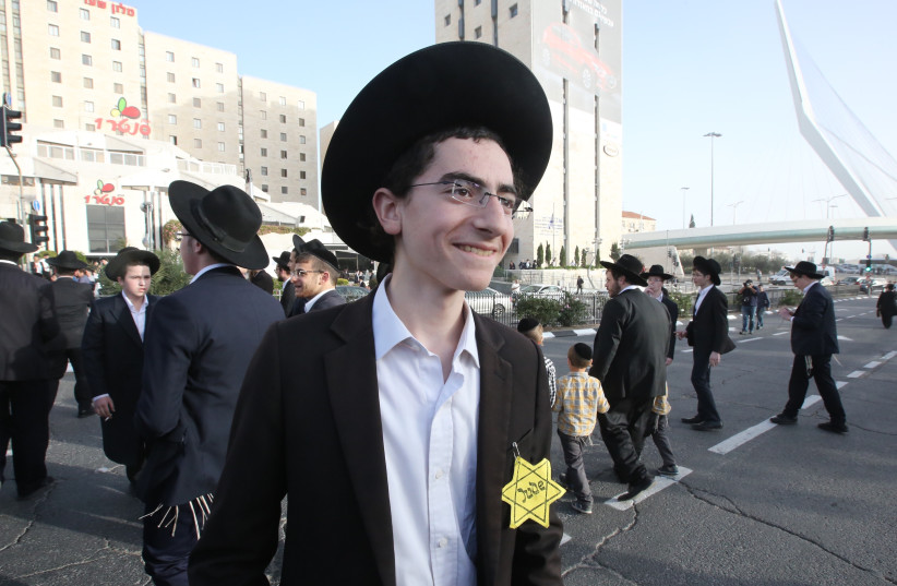 "A young haredi boy wearing a ""Jude"" star takes part in a protest against mandatory IDF conscription, March 2018 (photo credit: MARC ISRAEL SELLEM/THE JERUSALEM POST)"