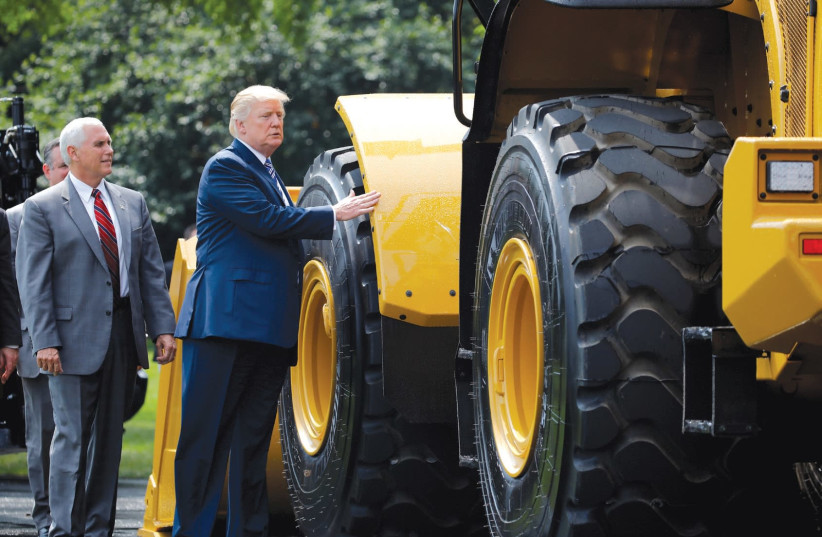 US PRESIDENT Donald Trump and Vice President Mike Pence stand next to Caterpillar equipment as they visit a 'Made in America' products showcase at the White House in July. (photo credit: CARLOS BARRIA / REUTERS)