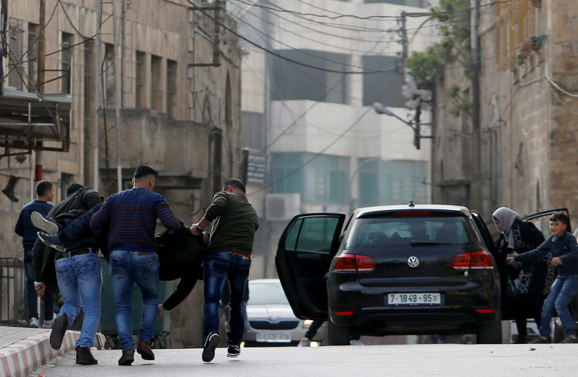 People evacuate a Palestinian who was shot dead during clashes with Israeli troops, in the West Bank March 9, 2018 (photo credit: REUTERS/MUSSA QAWASMA)