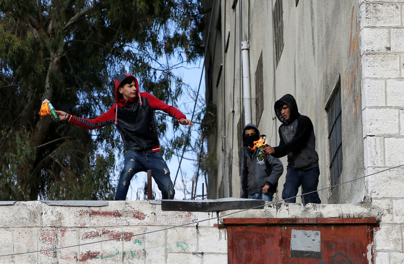 Palestinian demonstrators hurl molotov cocktails at Israeli troops during clashes at a protest against Trump's decision on Jerusalem, in Hebron, in the occupied West Bank March 9, 2018. (photo credit: MUSSA QAWASMA / REUTERS)