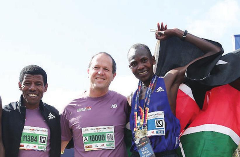Jerusalem Marathon winner Shadrack Kipkogey (right) next to Jerusalem Mayor Nir Barkat (center) and legendary Ethiopian runner Haile Gebrselassie (left)  (photo credit: Courtesy)