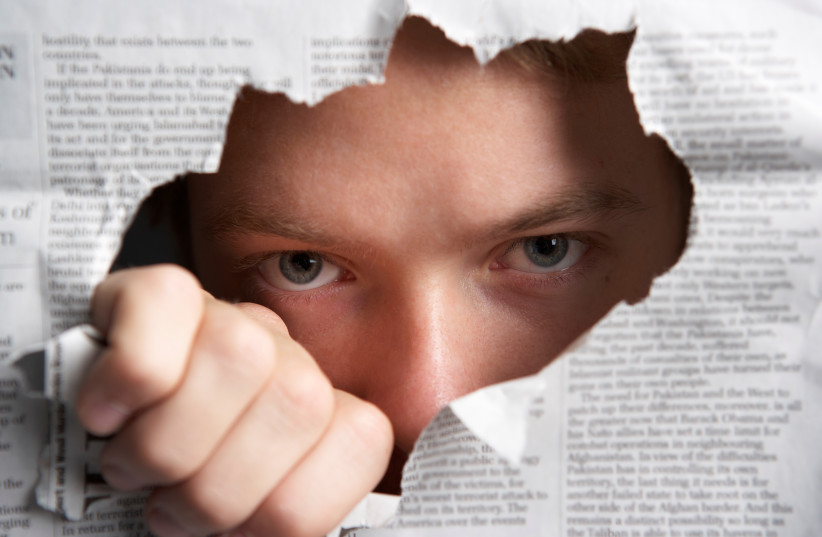 Man looking through hole in newspaper (Illustrative) (photo credit: INGIMAGE)