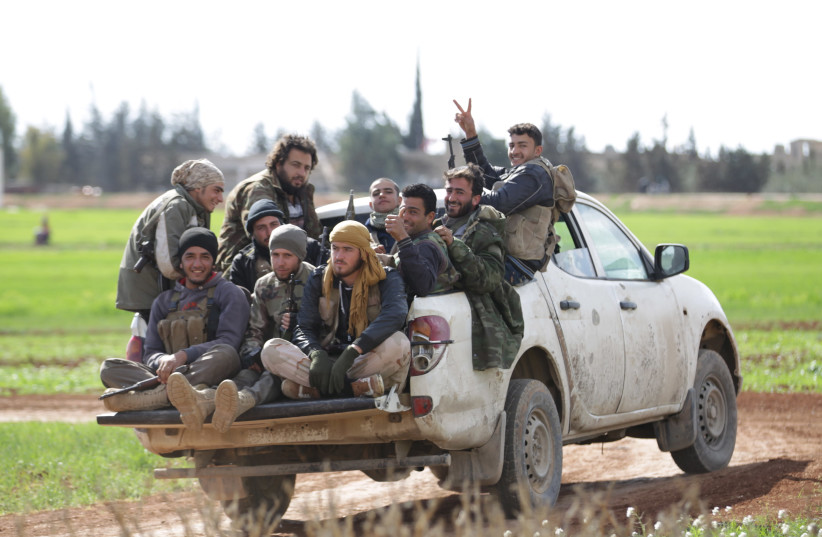 Rebel fighters from 'Jaysh al-Sunna' gesture as they ride a vehicle in Tel Mamo village, in the southern countryside of Aleppo, Syria (photo credit: KHALIL ASHAWI / REUTERS)