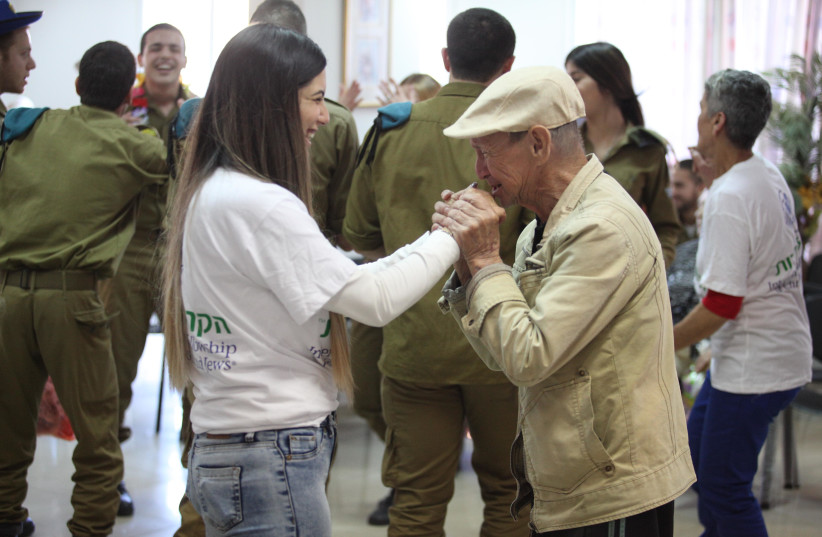 Fellowship volunteer dancing with an elderly man at a Purim party organized by the Fellowship in Lod last week (photo credit: DANIEL BAR ON)