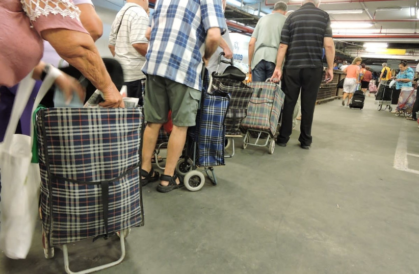 Needy people stand in line to buy food basket at the Pitchon Lev packaging and distribution center in Rishon LeZion (photo credit: YAKI ZIMERMAN)
