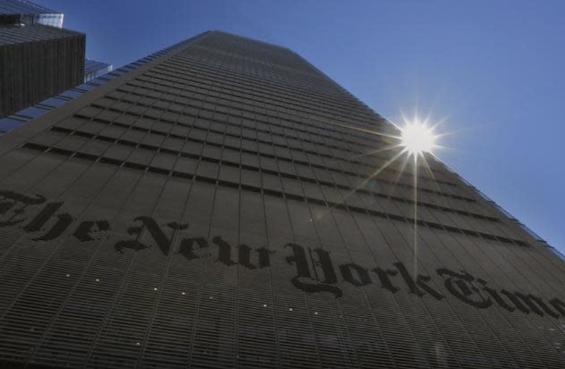 The sun peaks over the New York Times Building in New York August 14, 2013  (photo credit: BRENDAN MCDERMID/REUTERS)
