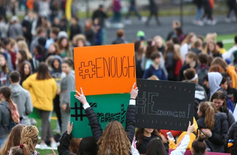 """Students hold """"#Enough"""" signs as they participate in the National School Walkout to protest gun violence in the U.S, March 14, 2018 (photo credit: REUTERS/LINDSEY WASSON)"""