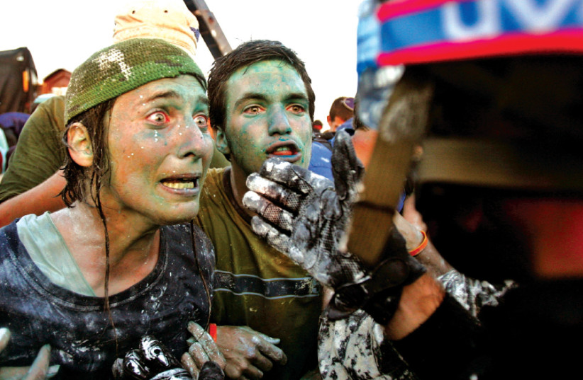 OPPONENTS OF Israel's disengagement plan from Gaza scream as they speak with a policeman in the settlement of Kfar Darom in the Gaza Strip in 2005 (photo credit: REUTERS/NIR ELIAS)
