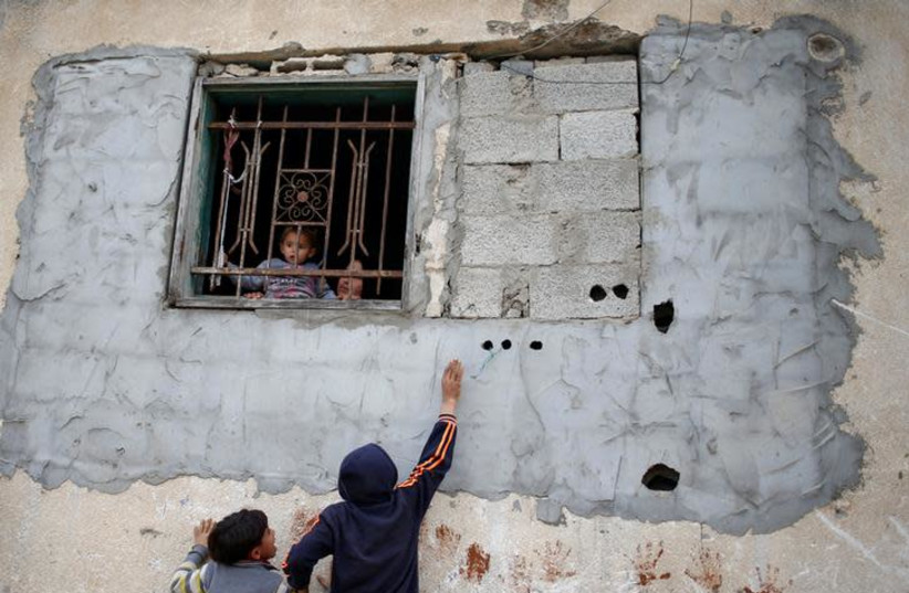Palestinian children play as a girl held by her mother looks out of the window of house in the northern Gaza Strip February 12, 2018. Picture taken February 12, 2018 (photo credit: MOHAMMED SALEM/REUTERS)