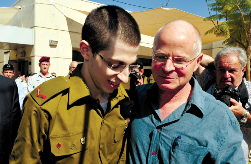 GILAD SCHALIT is reunited with his father, Noam, at the Tel Nof air base in 2011 after  ve years being held in captivity (photo credit: ARIEL HERMONI/IDF/REUTERS)