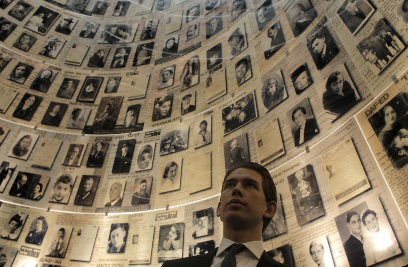 Austria's Foreign Minister Sebastian Kurz looks at pictures of Jews killed in the Holocaust during his visit to the Hall of Names at Yad Vashem's Holocaust History Museum in Jerusalem April 22, 2014 (photo credit: AMMAR AWAD / REUTERS)