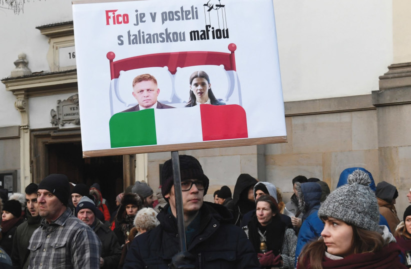 Participants hold a banner reading: 'PM Robert Fico in bed with Italian mafia' during a march in honor of murdered Slovak investigative reporter Jan Kuciak and his girlfriend, Martina Kusnirova, in Bratislava, Slovakia, in February (photo credit: REUTERS)