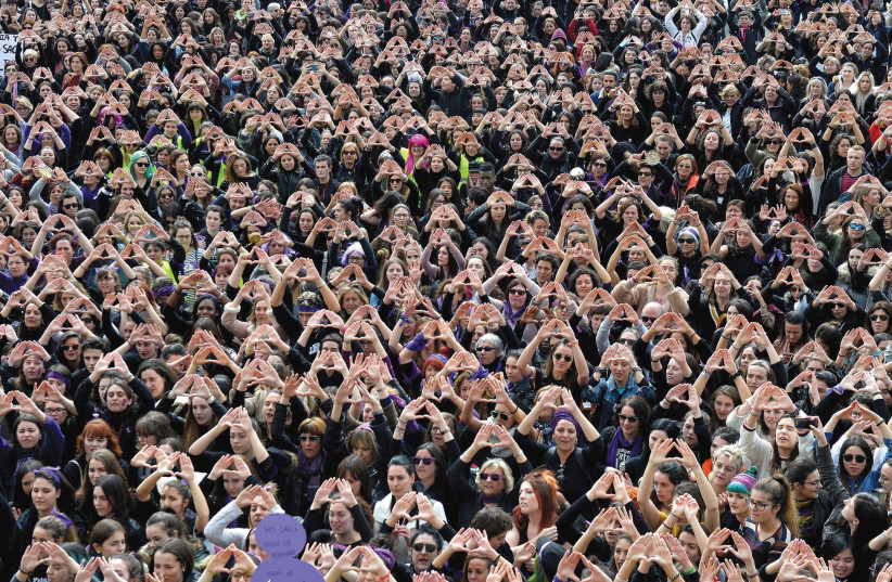Protesters form triangles with their hands during a demonstration for women's rights in Bilbao, Spain, on March 8, International Women's Day (photo credit: REUTERS)