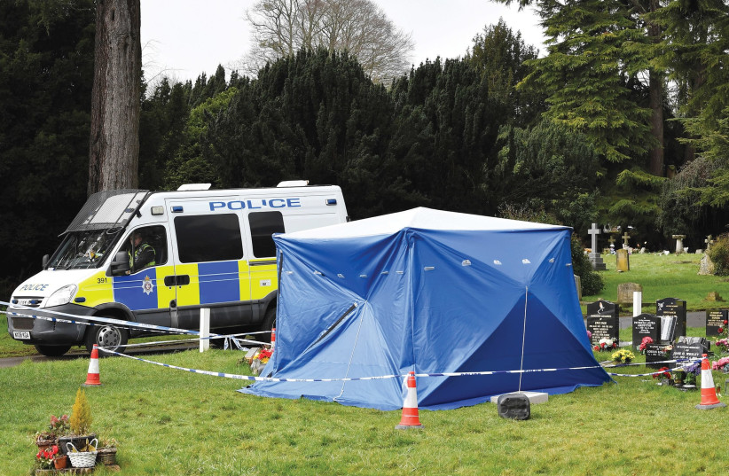 A police van is parked next to a tent covering the headstone of Alexander Skripal (photo credit: REUTERS)