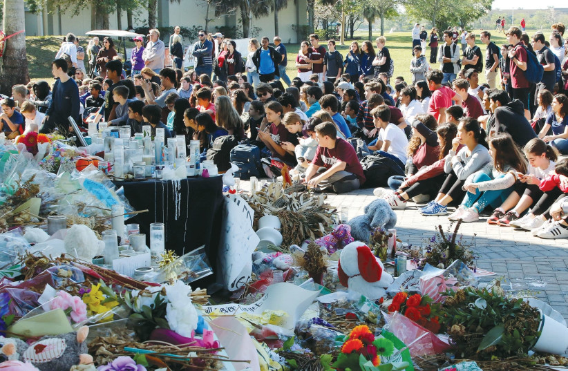 Students from Marjory Stoneman Douglas High School and Westglades Middle School gather near memorials at a park where they marched as part of a National School Walkout, to honor the 17 students and staff members killed at the high school in Parkland, Florida (photo credit: REUTERS)
