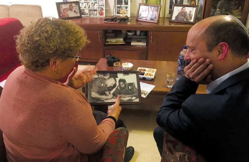 MIRIAM PERETZ shows a photo of her sons, who died in the service of the IDF, to Education Minister Naftali Bennett. (photo credit: Courtesy)