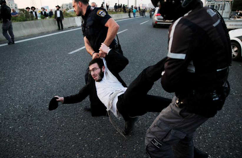 An Israeli ultra-Orthodox Jew is being carried away by police after blocking a main road in Bnei Barak during a protest (photo credit: AMMAR AWAD/REUTERS)