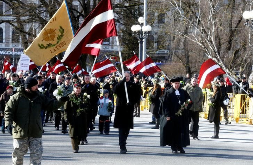 People participate in the annual procession commemorating the Latvian Waffen-SS (Schutzstaffel) unit, also known as the Legionnaires, in Riga, Latvia March 16, 2018 (photo credit: REUTERS/INTS KALNINS)