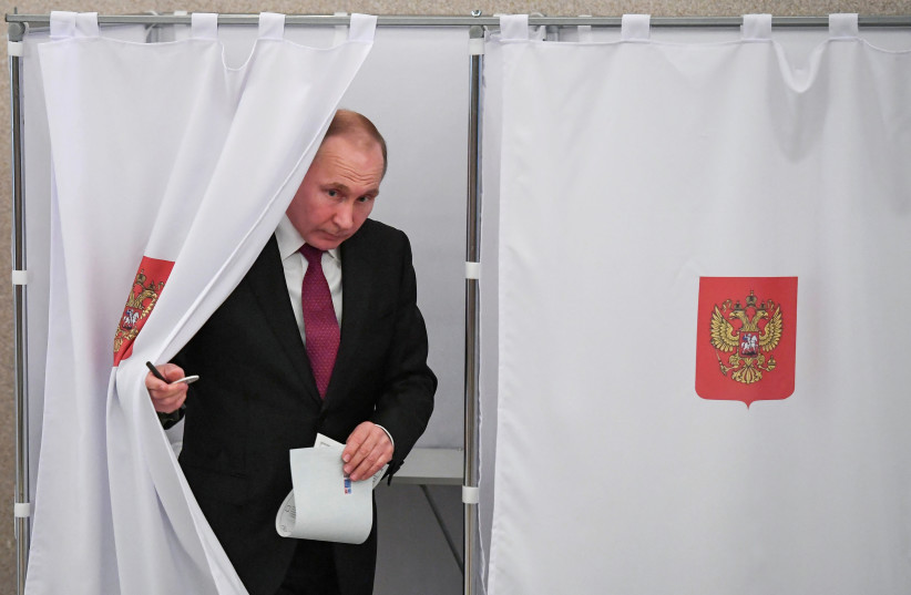 Russian President and Presidential candidate Vladimir Putin at a polling station during the presidential election in Moscow, Russia March 18, 2018 (photo credit: REUTERS/YURI KADOBNOV/POOL)
