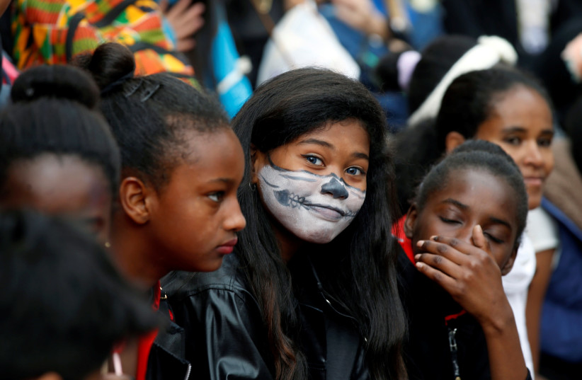 A girl looks at the camera during an event marking the Jewish holiday of Purim at the Bialik Rogozin school, where children of migrant workers and refugees are educated alongside native Israelis, in Tel Aviv, Israel March 10, 2017. (photo credit: BAZ RATNER/REUTERS)