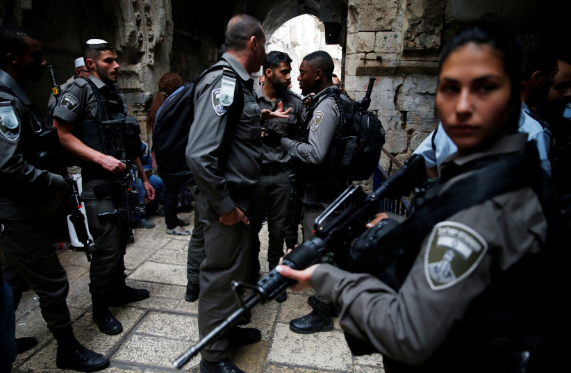 Israeli security forces stand at the site where an Israeli was killed in a stabbing attack in Jerusalem's Old City (photo credit: AMMAR AWAD / REUTERS)