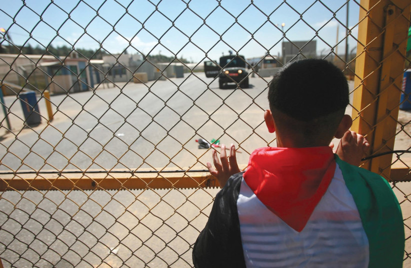 A young Palestinian stands outside Ofer Prison near Ramallah. B'Tselem finds fault with the way IDF West Bank courts treat minors who have been arrested (photo credit: FADI AROURI/REUTERS)