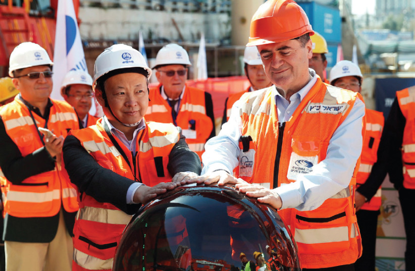 Transportation Minister Israel Katz and employees of China Railway Engineering Corporation join hands in an event marking the beginning of underground construction work of the light rail in Tel Aviv, 2018 (photo credit: BAZ RATNER/REUTERS)