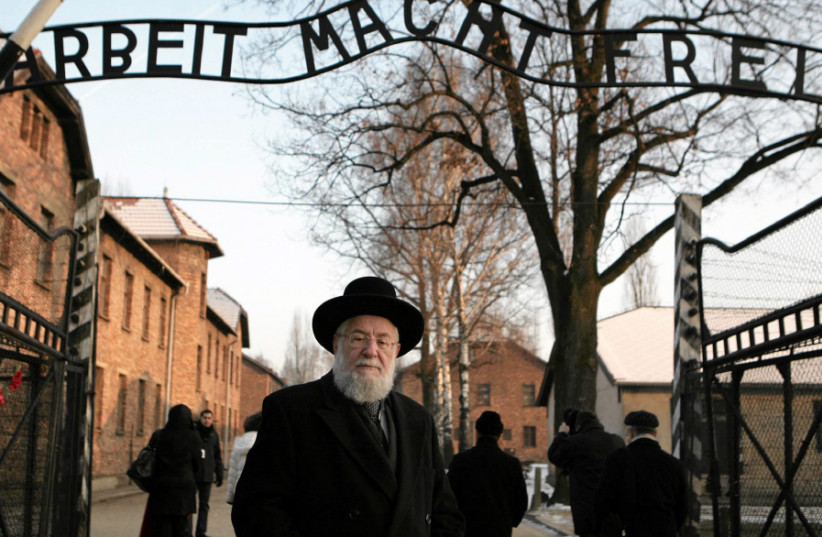 RABBI YISRAEL MEIR LAU stands at the main gate of the former Nazi death camp of Auschwitz with the words 'Arbeit macht frei' (Work sets you free), on February 1, 2011 (photo credit: MICHAL LEPECKI/AGENCIA GAZETA/REUTERS)