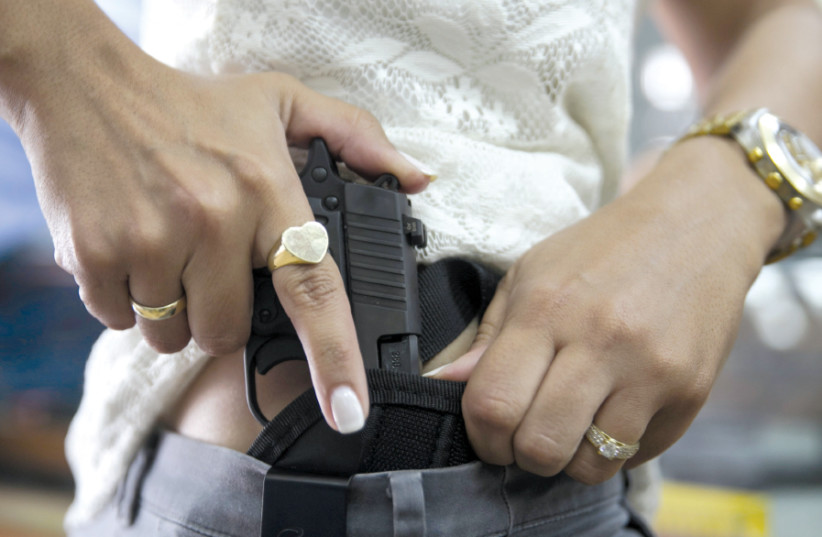 A WOMAN checks out a new pistol at a gun shop in Tel Aviv in 2015 (photo credit: BAZ RATNER/REUTERS)