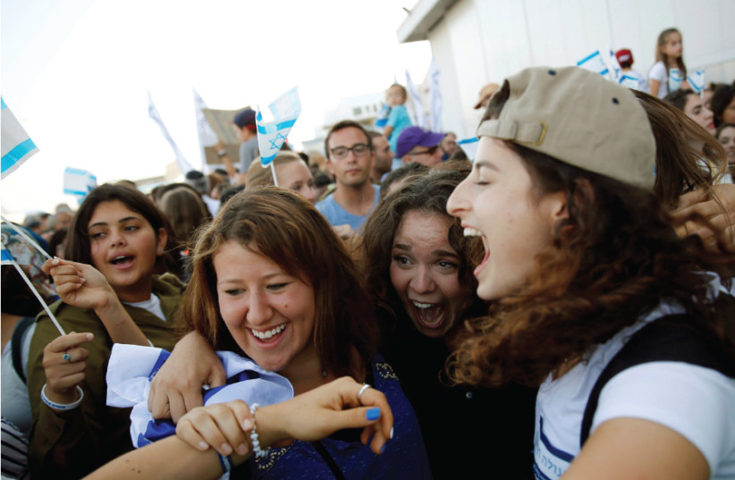 AN 'OLAH HADASHA' from North America (right) reacts as she is welcomed after landing at Ben-Gurion International Airport in 2016 (photo credit: BAZ RATNER/REUTERS)