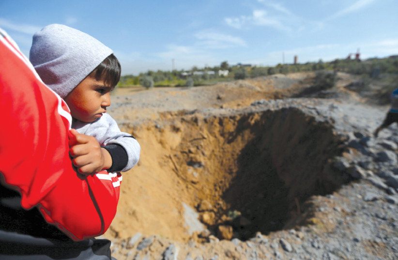 A PALESTINIAN boy is carried as he looks at the scene of an Israeli air strike, south of Gaza City, March 2018 (photo credit: IBRAHEEM ABU MUSTAFA/REUTERS)