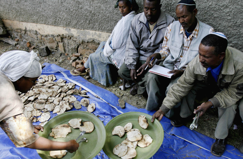 An Ethiopian Jewish woman gives matzahto a man ahead of Passover at a compound while awaiting immigration to Israel in Gondar March 9, 2007  (photo credit: ELIANA APONTE/REUTERS)
